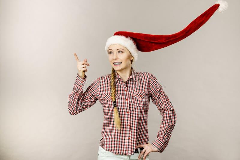 Pozytywna dziewczyna jest ubranym dmuchający Santa Claus kapelusz fotografia royalty free
