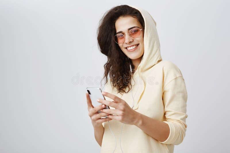 Pozytywna ekspresyjna dziewczyna jest ubranym żółtego hoodie i modnych okulary przeciwsłonecznych ono uśmiecha się szeroko przy k obraz royalty free