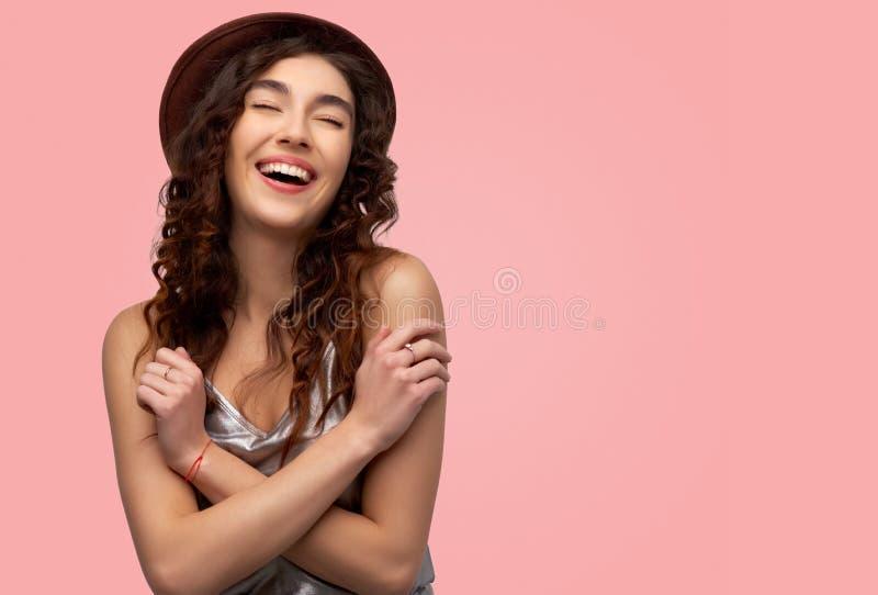 Pozytywna i radosna młoda dziewczyna utrzymuje oba ręki na krzyżu, być w dobrym nastroju fotografia stock