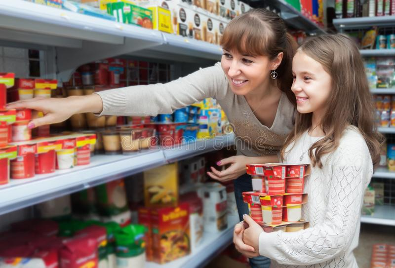 Pozytywna kobieta z córki kupienia jogurtami fotografia royalty free