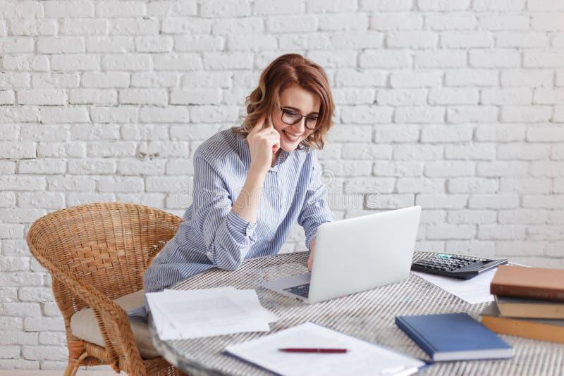 Pozytywna młoda kobieta opowiada na telefonicznym obsiadaniu przy laptopem w nowożytnym biurze fotografia stock