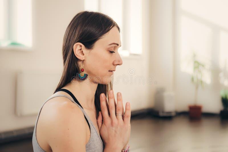 Pozytywna młoda kobieta robi namaste ręki gestowi przy studiiem obraz stock