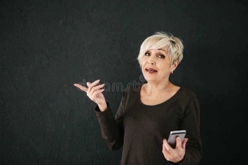 Pozytywna nowożytna starsza kobieta trzyma telefon komórkowego i używa je Nowożytna technologia i zdjęcie stock