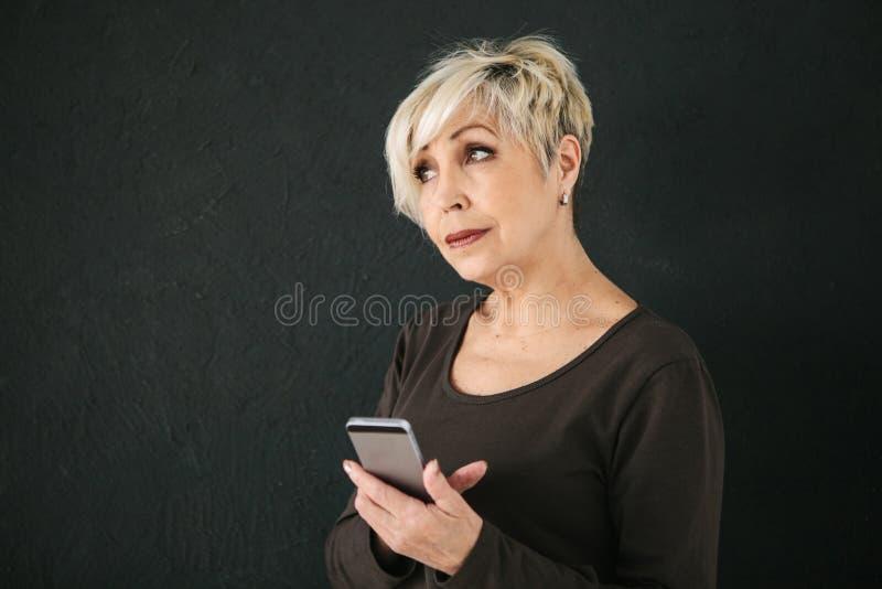 Pozytywna nowożytna starsza kobieta trzyma telefon komórkowego i używa je Nowożytna technologia i zdjęcia royalty free