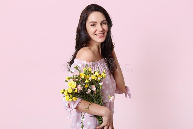 Pozytywna optymistycznie brunetki młoda dama otrzymywa kwiaty na urodziny, jest ubranym polki kropki elegancką suknię, ono uśmiec zdjęcie stock