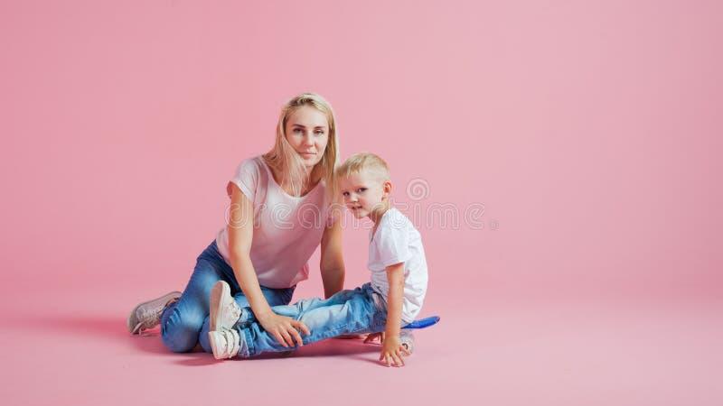 Pozytywna potomstwo matka z młodym synem Piękna blondynka z jej dzieckiem na deskorolka obraz royalty free