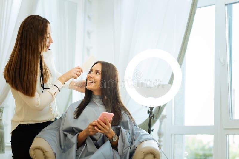 Pozytywna radosna kobieta patrzeje jej włosianego stylisty zdjęcie royalty free