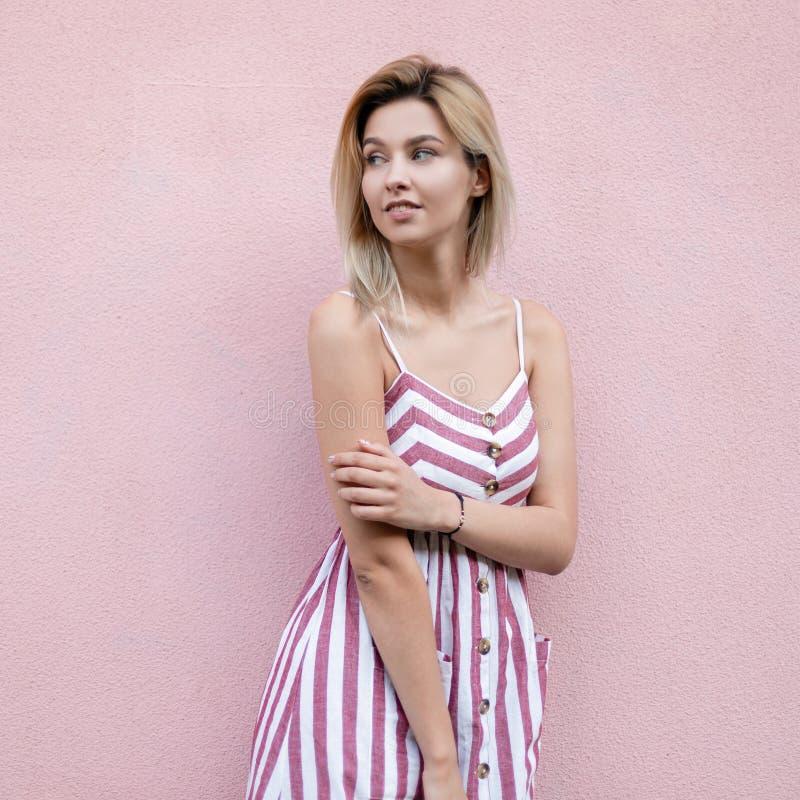 Pozytywna radosna młoda kobieta z blondynem z błękitnymi pięknymi oczami z ślicznym uśmiechem w modnym lecie paskował sundress sp obraz stock