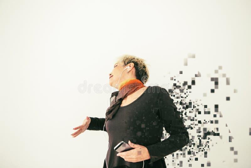 Pozytywna starsza kobieta słucha muzyka, tanczy i śpiewa, Rozpraszający pikslami Nowy i obrazy royalty free