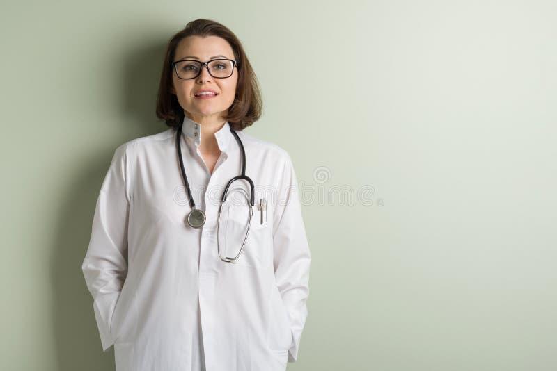 Pozytywna w średnim wieku kobiety lekarka, jest ubranym szkła Tło zieleni ściana w klinice obrazy stock