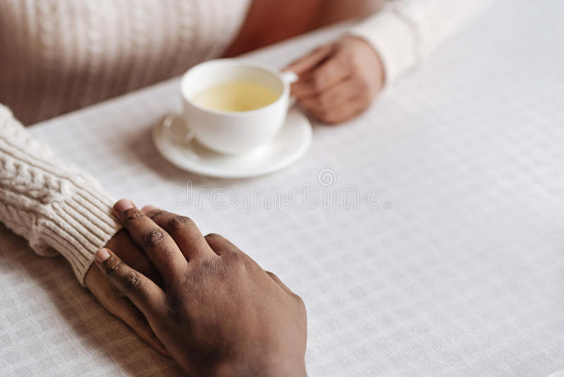 Pozytywne amerykanin afrykańskiego pochodzenia pary mienia ręki w kawiarni zdjęcia royalty free