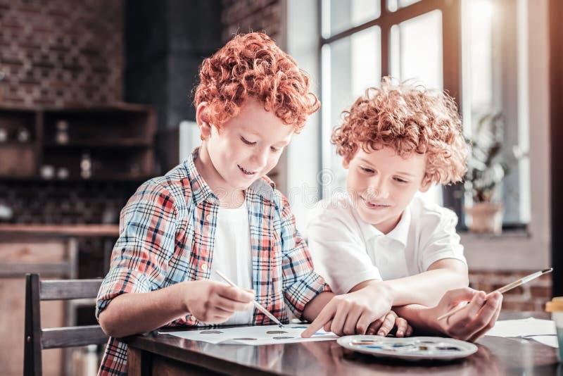 Pozytywne utalentowane chłopiec maluje obrazek obraz stock