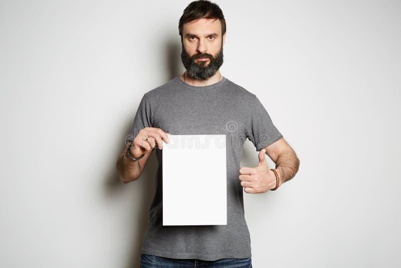 Pozytywnego brutalnego tatuującego brodatego faceta mienia pustego prześcieradła papierowa i pusta szara koszulki premii lata  zdjęcie royalty free