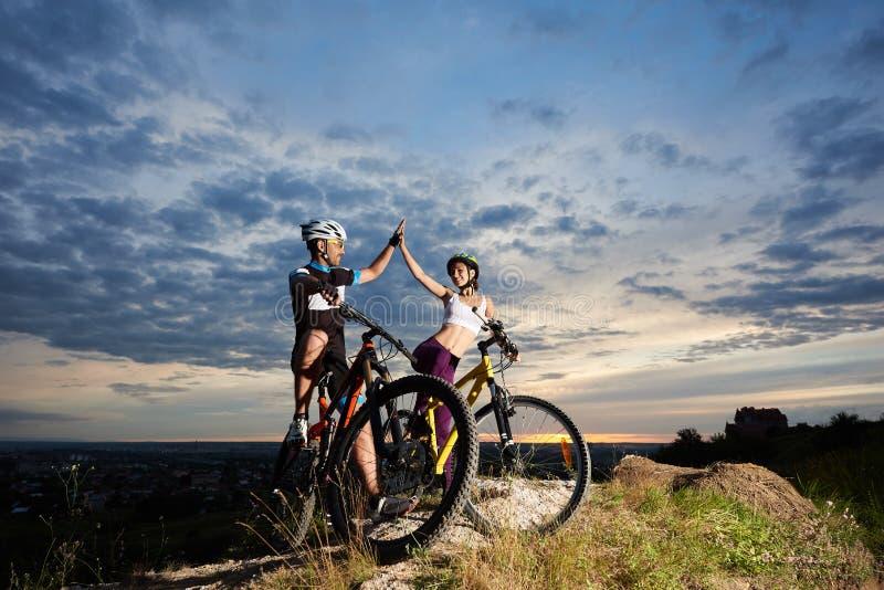 Pozytywni cykliści uśmiecha się pięć na rowerach i highing obraz royalty free