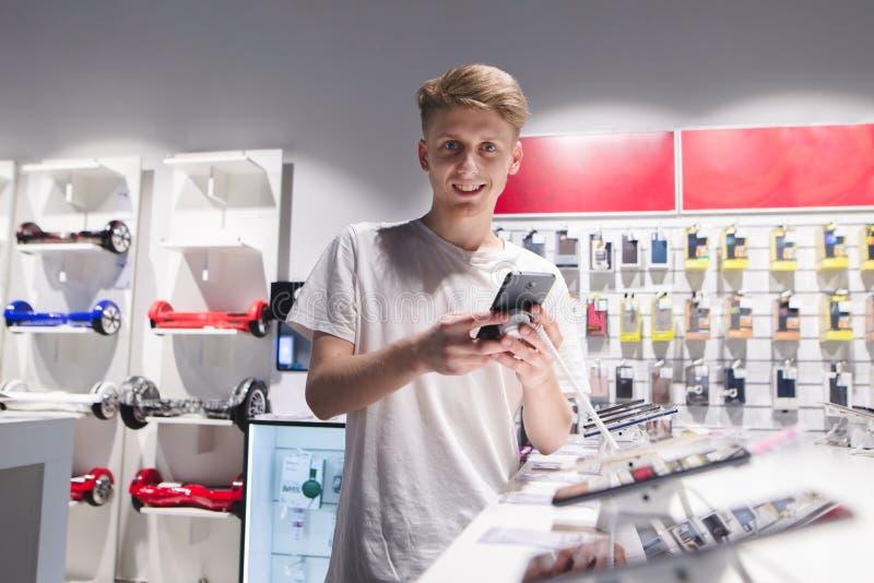 pozytywni młodych człowieków stojaki z smartphone w elektronika sklepie, spojrzenia przy kamerą i uśmiechy, obraz royalty free