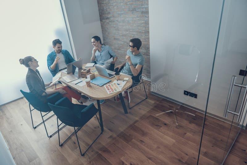 Pozytywni mężczyźni i kobiety opowiadają w workroom obraz stock