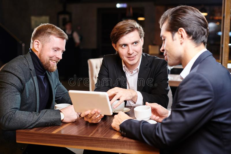 Pozytywni partnery biznesowi dyskutuje projekt w restauracji fotografia stock