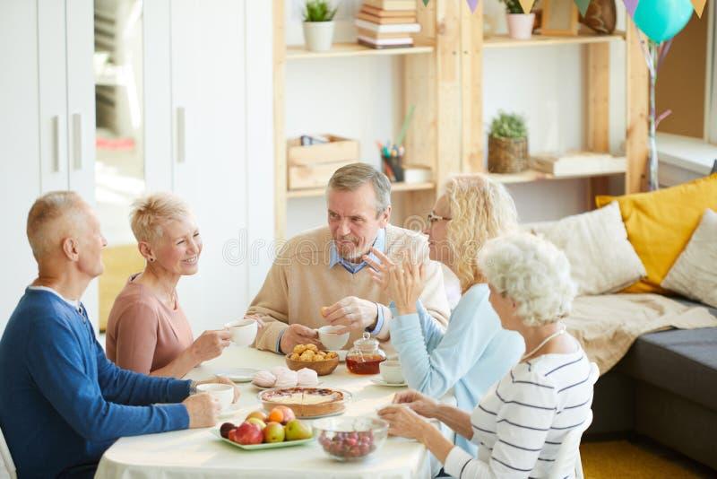 Pozytywni przyjaciele gawędzi przy stołem zdjęcia royalty free