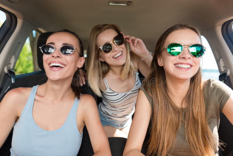 Pozytywni uśmiechnięci przyjaciele jedzie samochód zdjęcia stock