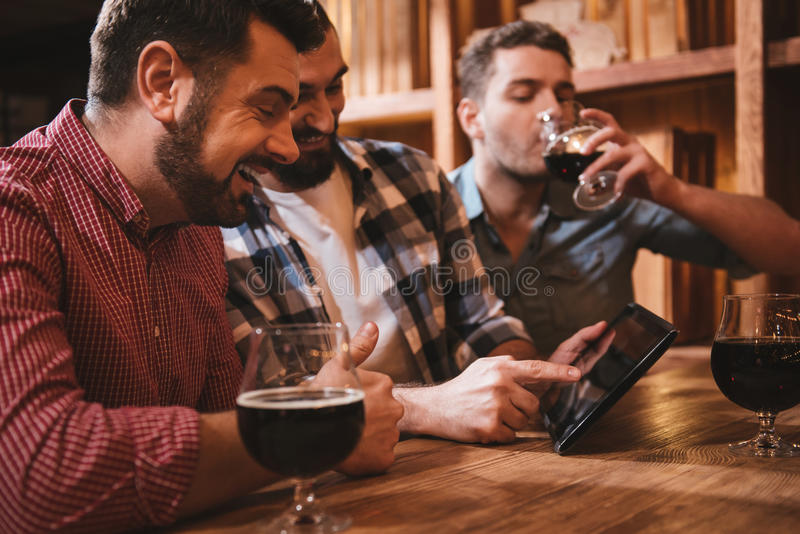 Pozytywny ładny mężczyzna patrzeje pastylka ekran fotografia stock