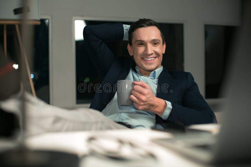 Pozytywny agent nieruchomości cieszy się kawę fotografia stock