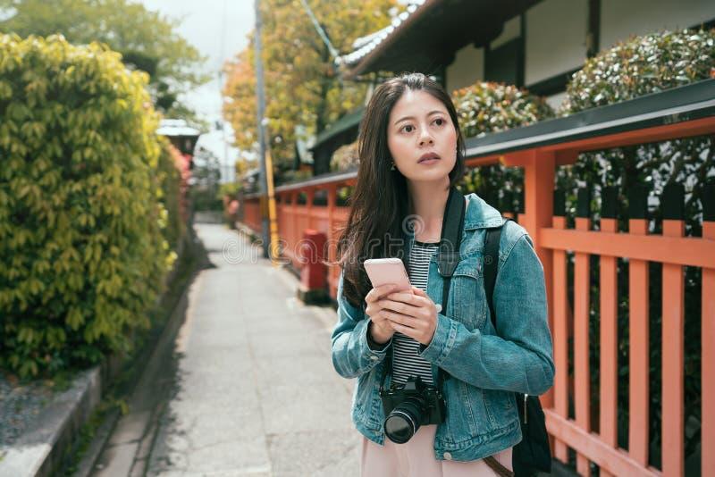 Pozytywny azjatykci dziewczyna podróżnik używa smartphone obraz royalty free