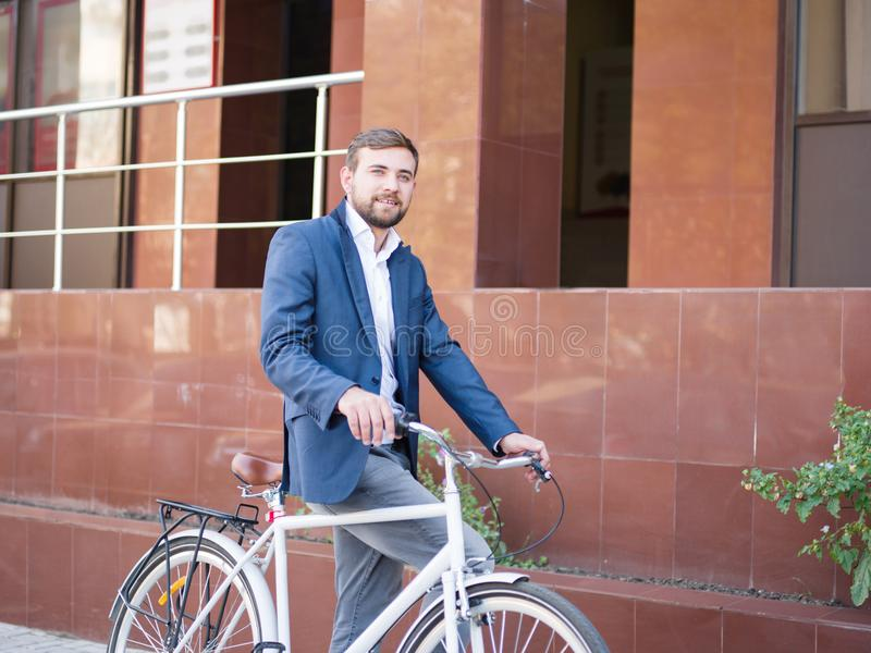 Pozytywny biznesowy mężczyzna z bicyklem na miasta tle samolotowy pojęcia eco transport kosmos kopii obraz stock