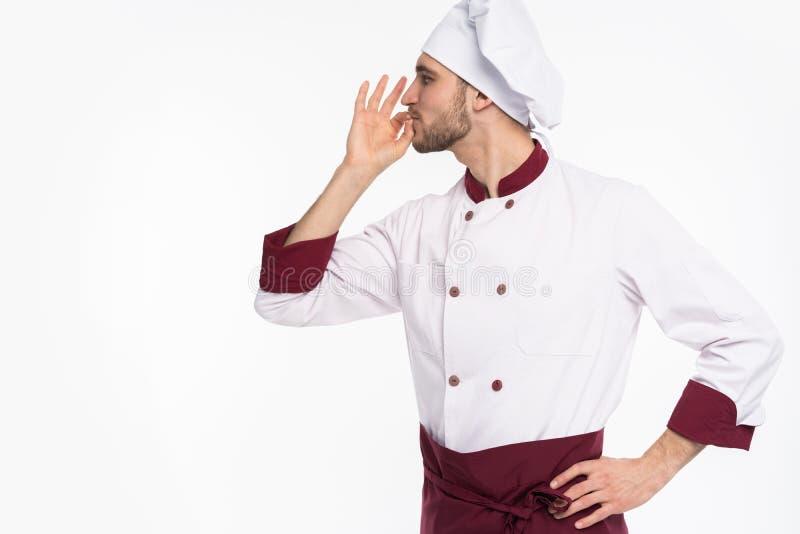 Pozytywny fachowy szczęśliwy mężczyzny szef kuchni pokazuje smakowitego ok znaka odizolowywającego na białym tle zdjęcia stock