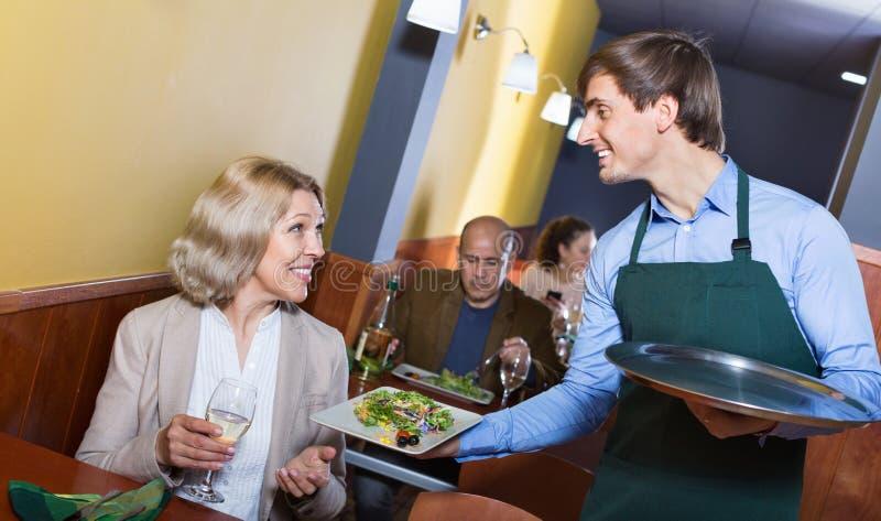 Pozytywny kelnera dowiezienia rozkaz uśmiechnięta dojrzała kobieta zdjęcie stock