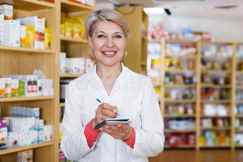 Pozytywny kobieta sprzedawcy writing asortyment w sklepie zdjęcie royalty free