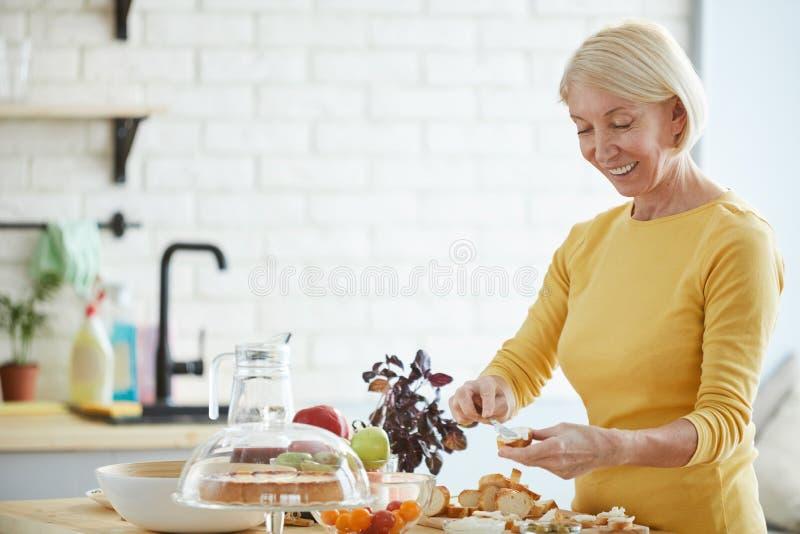 Pozytywny kobiety narządzania bruschetta w kuchni obraz stock