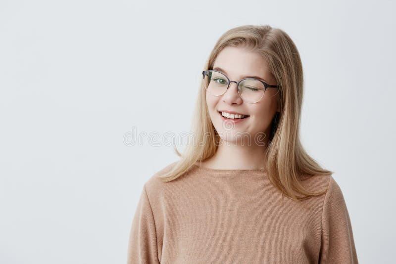 Pozytywny kokieteryjny Europejski żeński uczeń ono uśmiecha się szczęśliwie z blondynka prostym włosy, mrugający przy kamerą w fi fotografia royalty free