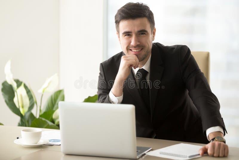 Pozytywny lider biznesu pozuje przy biurkiem w biurze zdjęcie stock