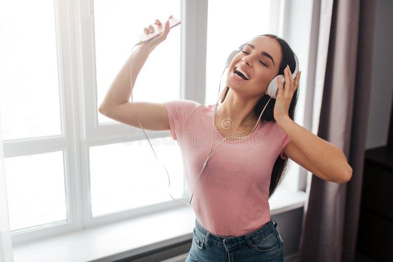 Pozytywny młoda kobieta stojak i słucha muzyka przez hełmofonów w pokoju Tanczy i cieszy się Wzorcowy Uśmiech Trzyma zdjęcie stock