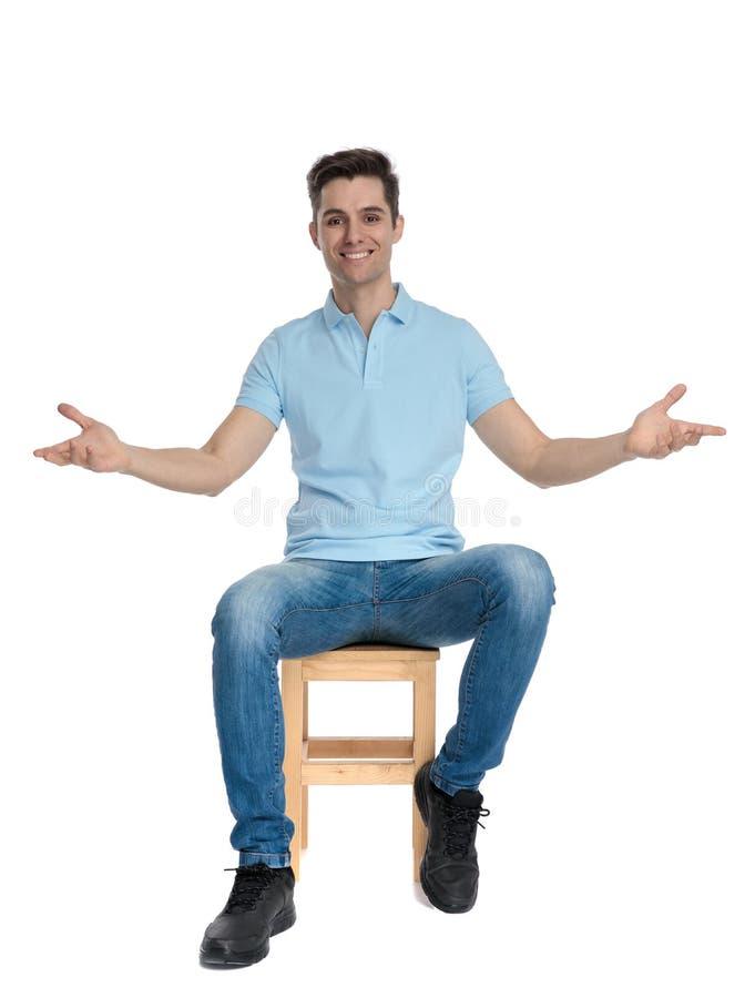 Pozytywny młodego człowieka obsiadanie z jego zbroi szeroko otwarty obraz stock