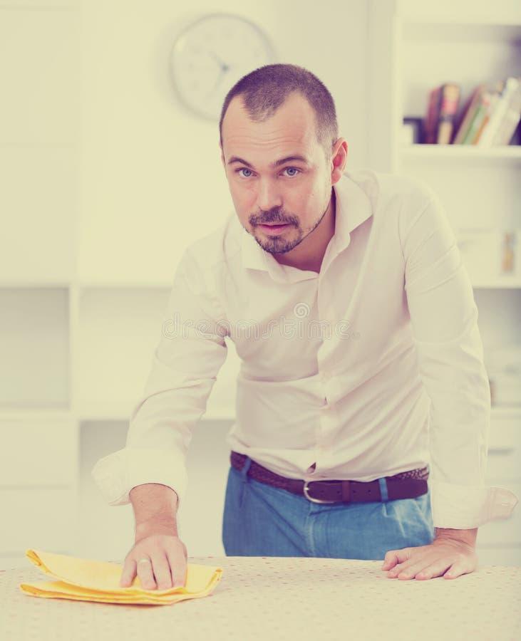 Pozytywny młody człowiek czyści biurowego biurko zdjęcia royalty free