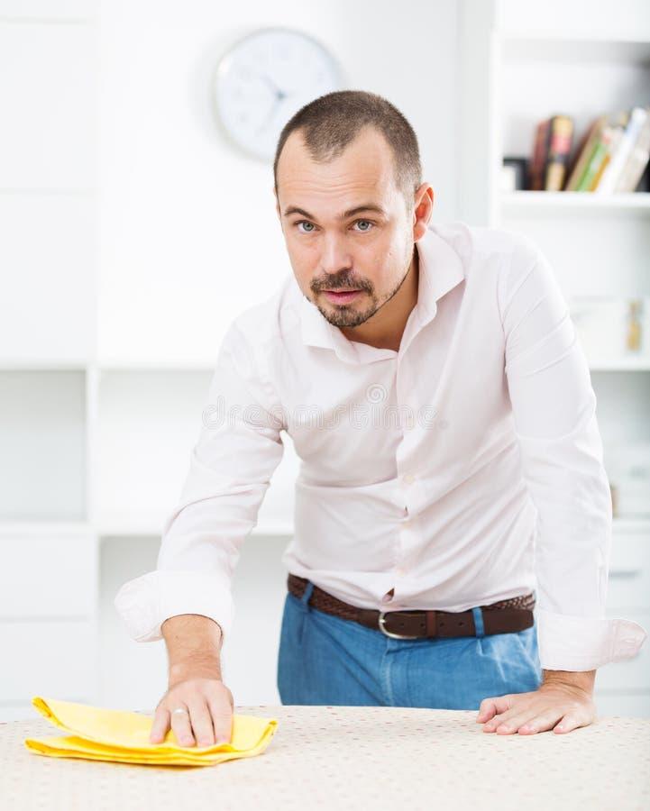 Pozytywny młody człowiek czyści biurowego biurko obraz stock
