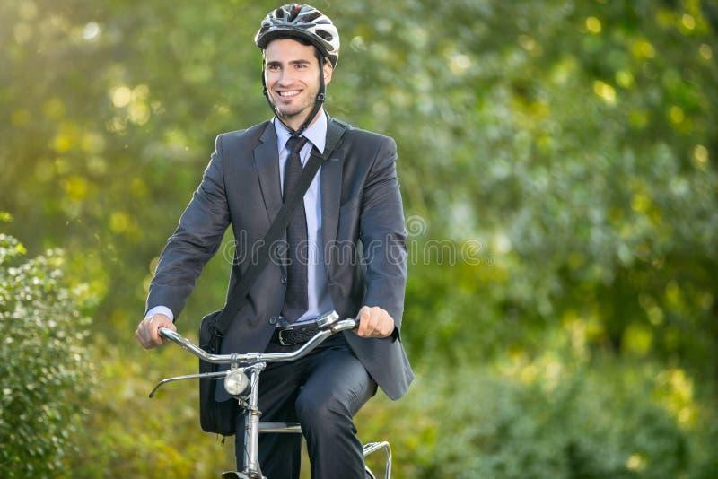 Pozytywny młody człowiek jedzie bicykl pracować fotografia royalty free