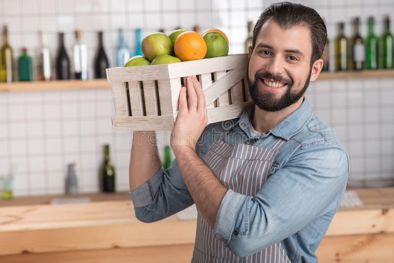 Pozytywny młody pracownik trzyma ciężkiego pudełko z różnorodną smakowitą owoc fotografia stock