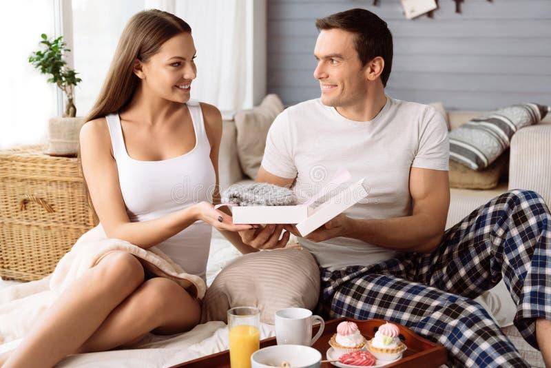 Pozytywny przystojny mężczyzna daje teraźniejszości jego dziewczyna obraz stock