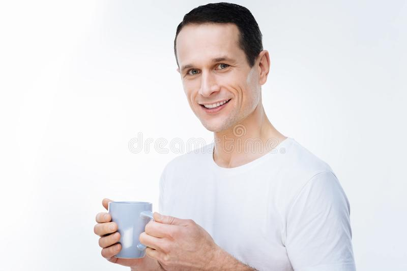 Pozytywny przystojny mężczyzna pije herbaty obraz royalty free
