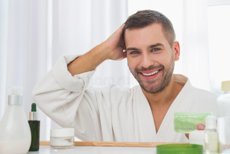 Pozytywny przystojny mężczyzna trzyma butelkę włosiany gel zdjęcia stock