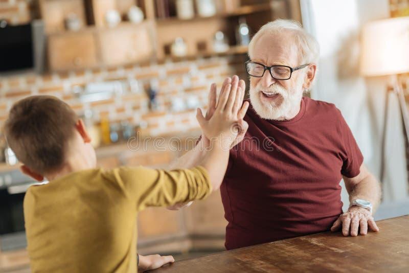 Pozytywny radosny dziad i wnuk daje wysokości pięć obraz royalty free