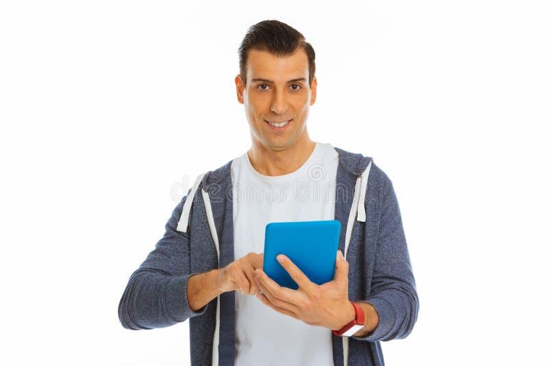 Pozytywny radosny mężczyzna używa nowożytnego technologicznego przyrząd zdjęcie royalty free