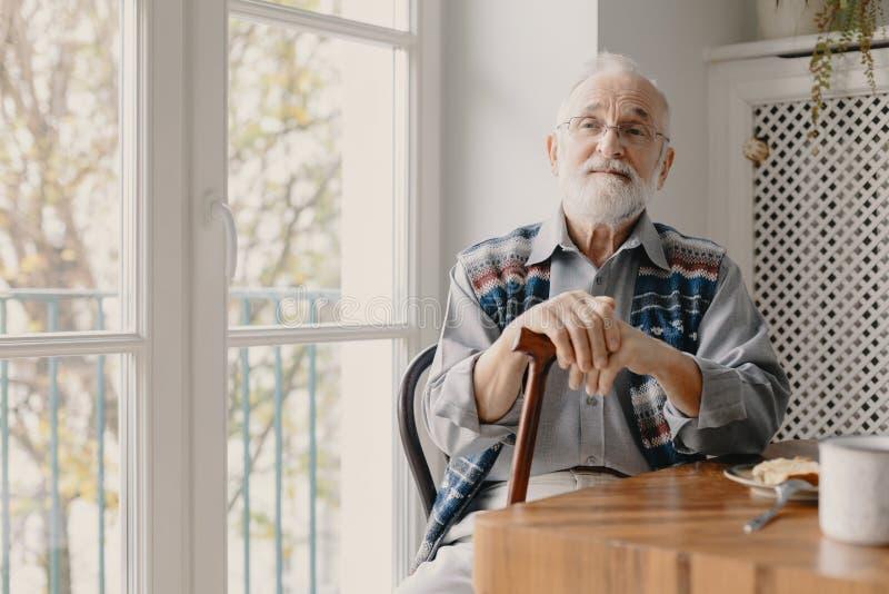 Pozytywny starszy dziad siedzi w domu z popielatym w?osy i broda zdjęcie stock