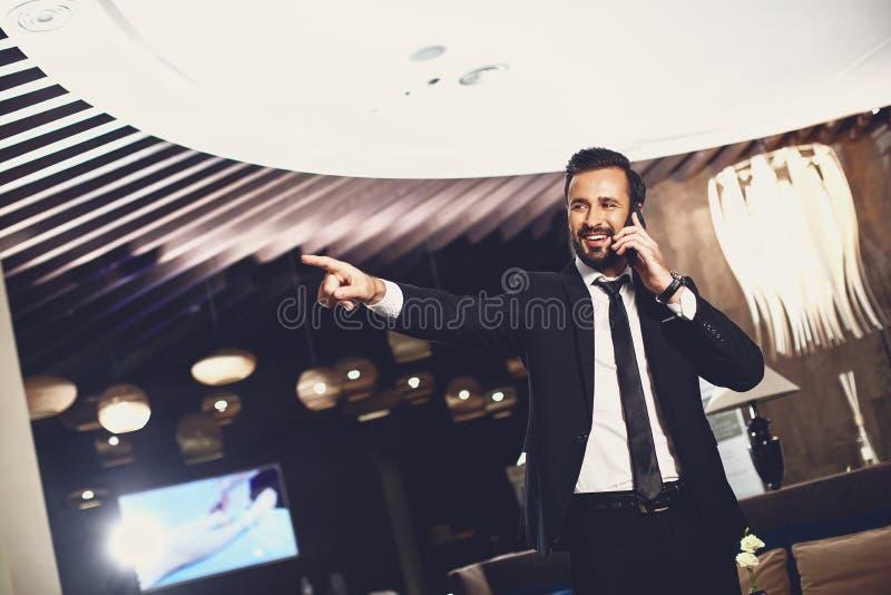 Pozytywny stylowy mężczyzna wskazujÄ…cy odlegÅ'ość i rozmawiajÄ…cy przez telefon zdjęcie royalty free