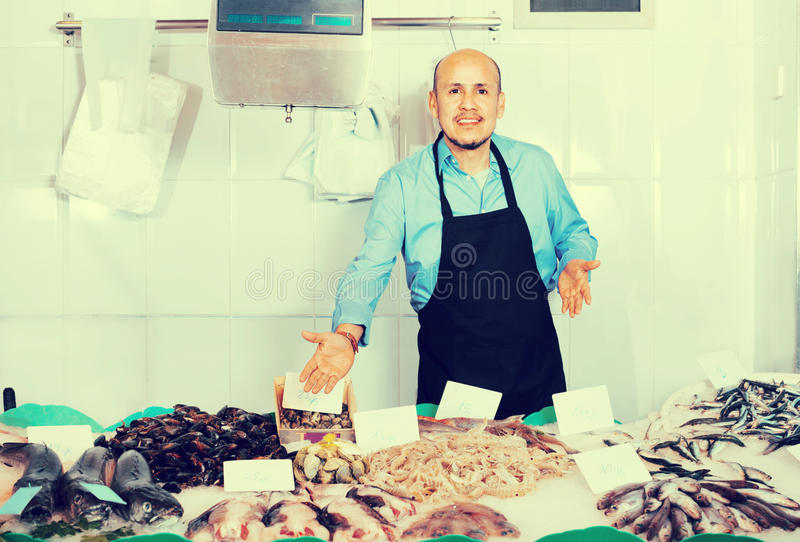 Pozytywu dojrzały sprzedawca oferuje świeżej ryba z fartuchem obraz royalty free