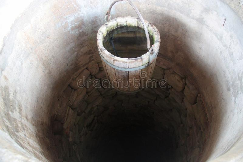 Pozzo d'acqua delle pietre con il secchio di legno fotografia stock