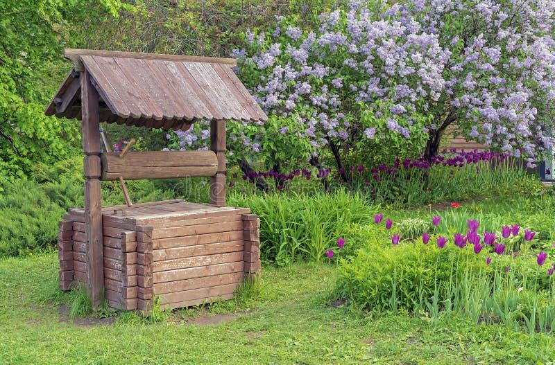 Pozzo di legno contro lo sfondo dei lillà di fioritura Pozzo di legno nella campagna immagine stock libera da diritti