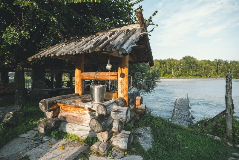 Pozzo paesino tradizionale sullo sfondo di una bellezza naturale con un fiume di montagna Estrazione manuale del prodotto nel ris immagine stock